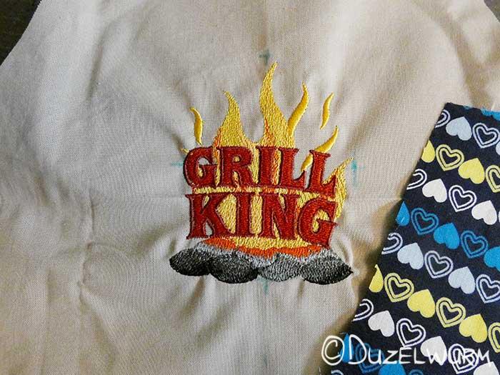 Stickbild Grill King auf der unifarbenen Schürze